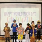 Seven school children wearing different costumes, stood in front of a projector screen.