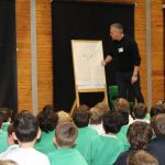Children sat on the floor watching a teacher drawing on a giant notepad.