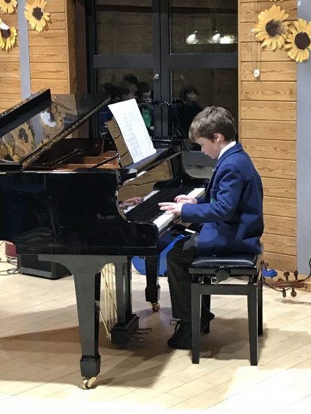 A boy wearing a blue blazer, sat down playing a grand piano.