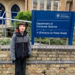 A child stood outside a sign for the Department of Computer Science at The University of Oxford.
