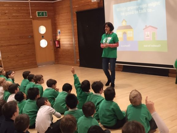 Kids sat on a school hall floor, watching a teacher give a presentation. They are all wearing green tops.