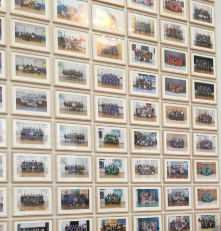 A collection of school class photos pinned up on a wall.